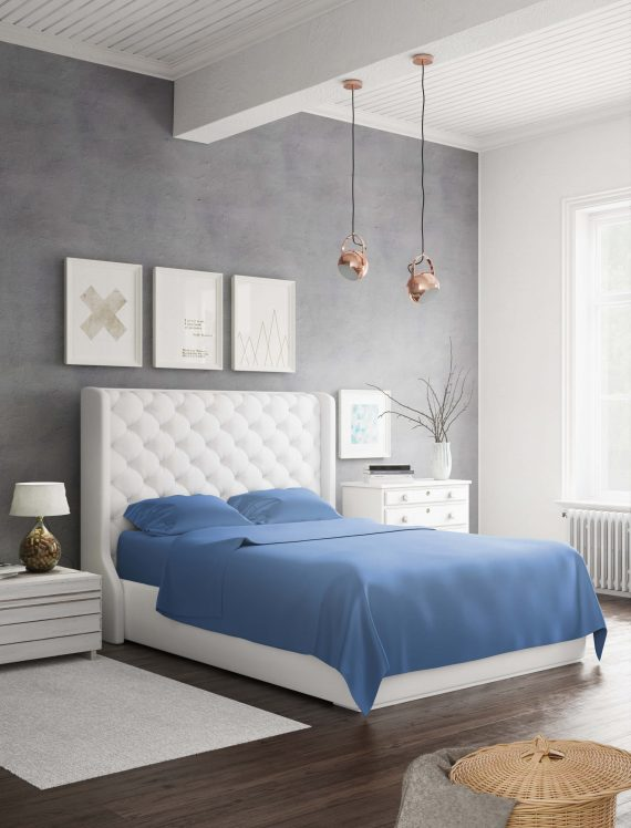 A white bed in a room using bamboo blend sheets in darkblue