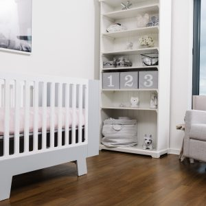 A white crib in a room using the softest pink bamboo crib sheets