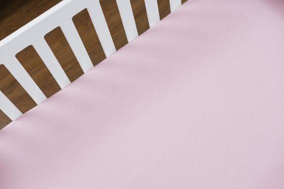 A crib using pink cotton crib sheets