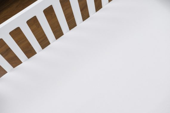 Close-up of a white crib using white bamboo crib sheet