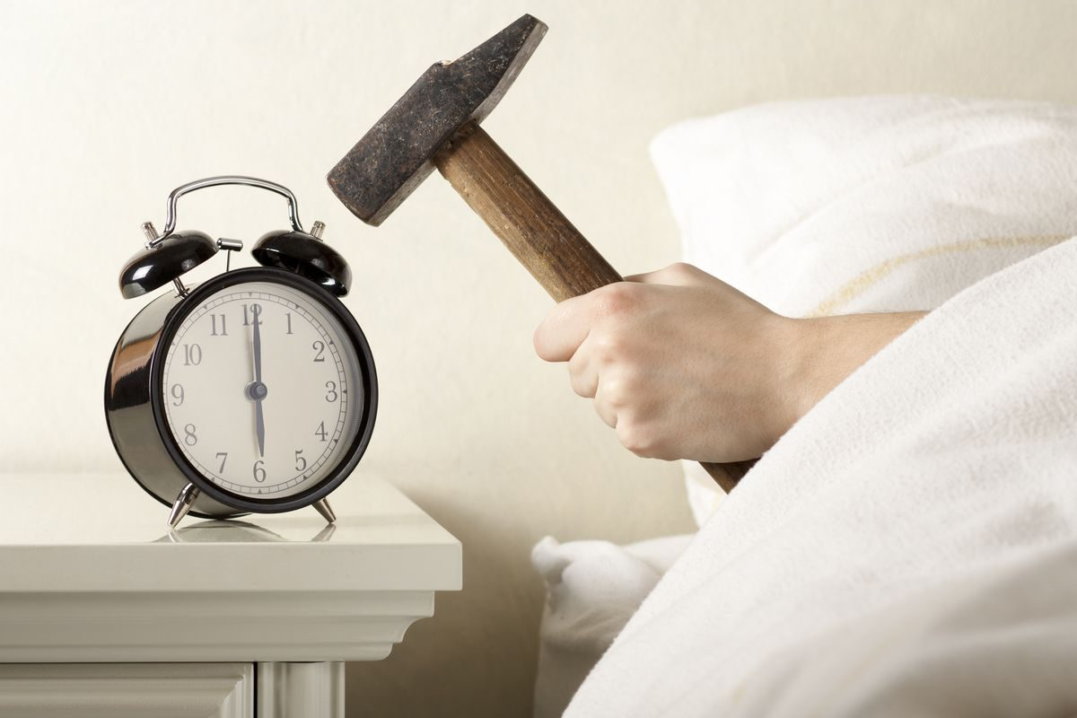 A hand holding a hammer to pound an alarm clock is one of the ways to get yourself out of bed quickly